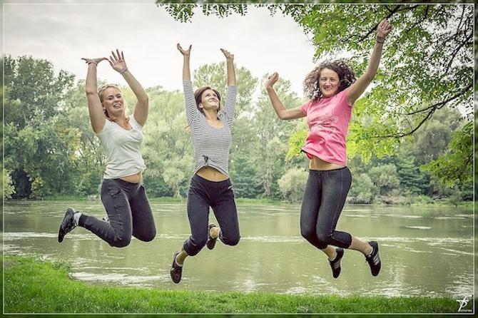 tre glade kvinner hopper, natur som bakgrunn