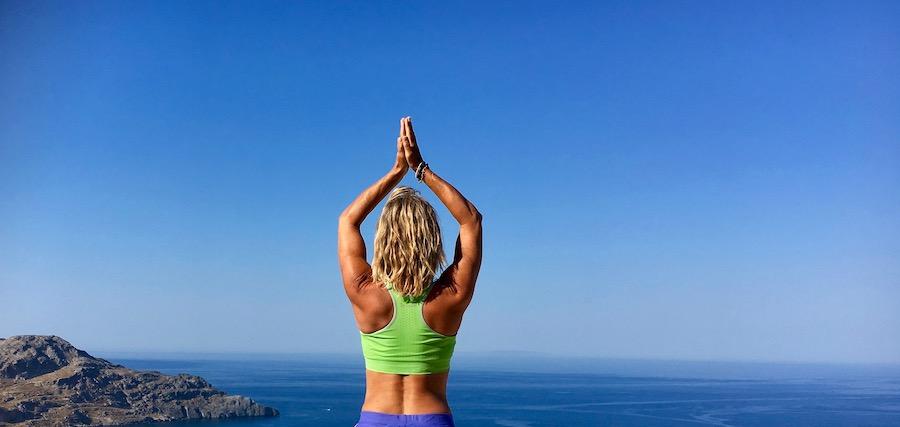 kvinne avbildet bakfra, hun har armene hevet, samlede hender, bakgrunn av hav og himmel