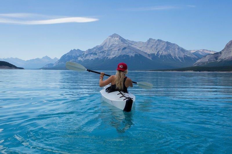jente i kajakk padler, fjell og himmel som bakgrunn