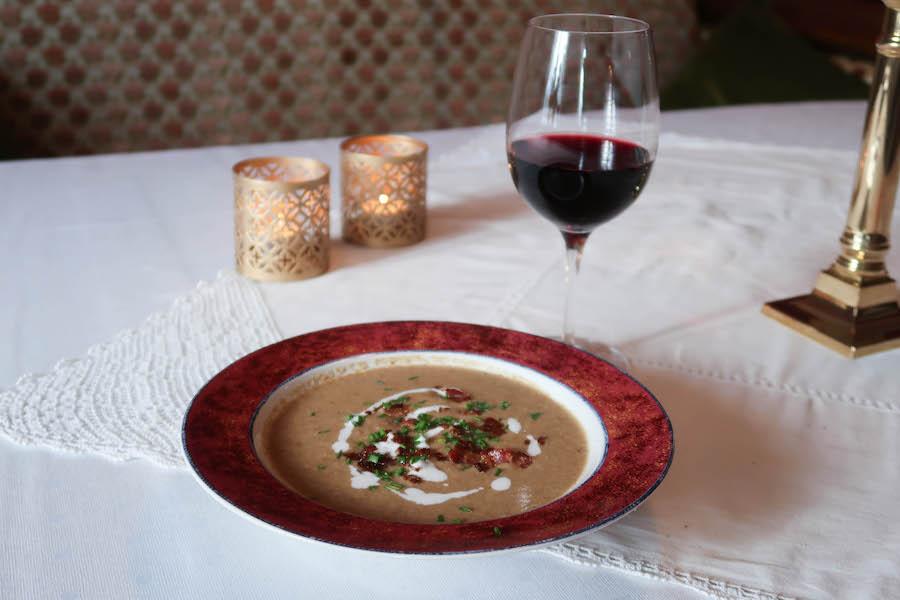 skål med soppsuppe på bord med hvit duk, rødvinsglass i bakgrunnen