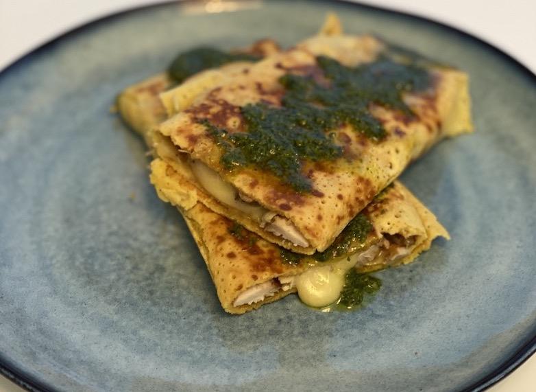 pannekaker sammenrullet med fyll av ost og avokado, med pesto på toppen