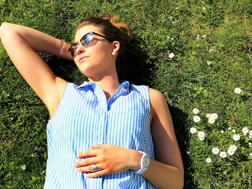 kvinne soler seg på grønn eng med blomster