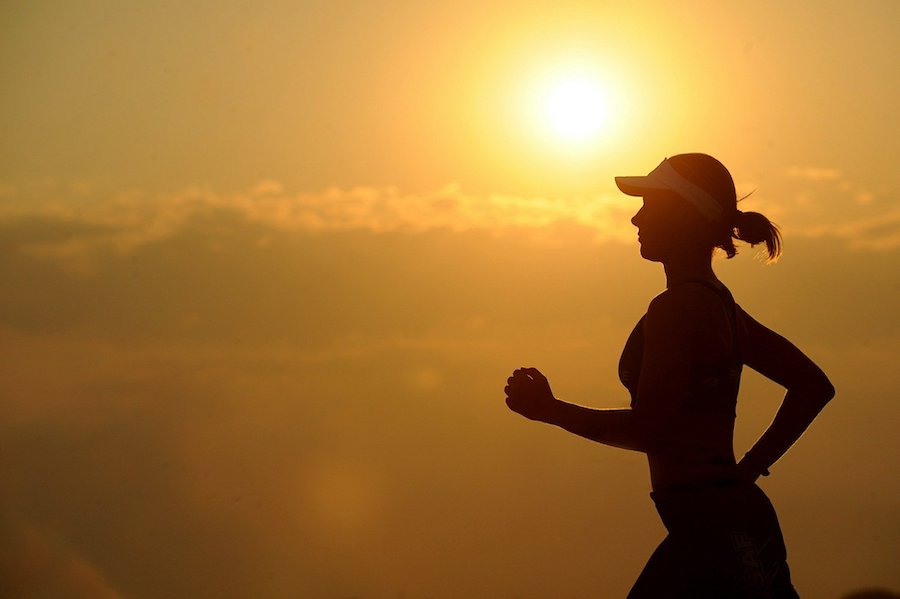 kvinne som løper, hun er vist i silhuett, bakgrunnen er solnedgang