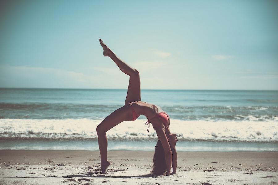kvinne på strand, i yogaposisjon med et ben hevet