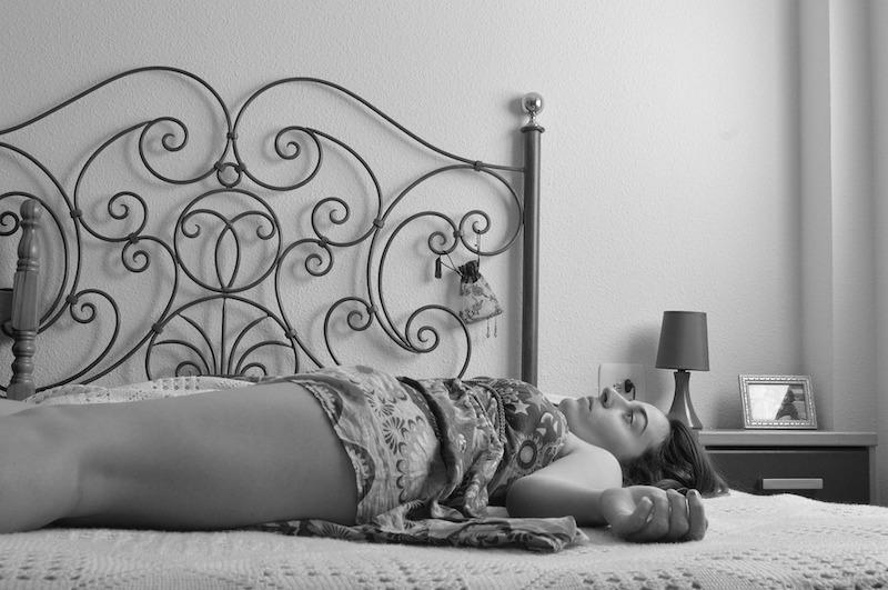 kvinne ligger på en seng med ornamenter, bildet i sorthvitt