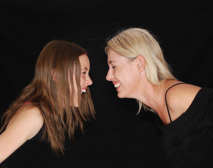 Ung kvinne og voksen kvinne ser på hverandre, profil, sort bakgrunn