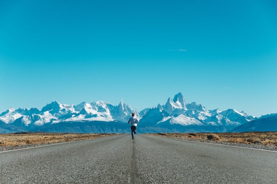 løping, mann løper på rak vei, snøkledde fjell i bakgrunnen