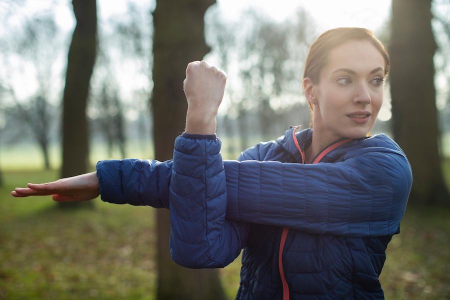 Kvinne strekker ut etter trening, morgensol og park