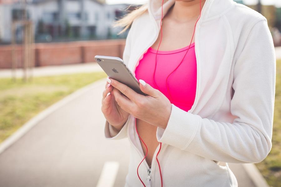 trening: kvinne med rosa topp og hvit jakke, kikker på mobilen sin