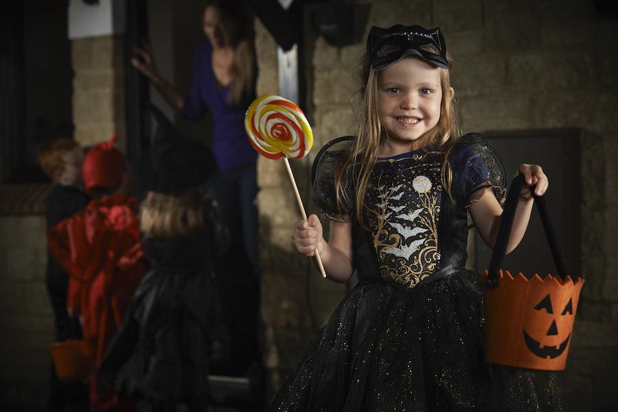 Jente i kostyme, Halloween, godteri i den ene hånden.