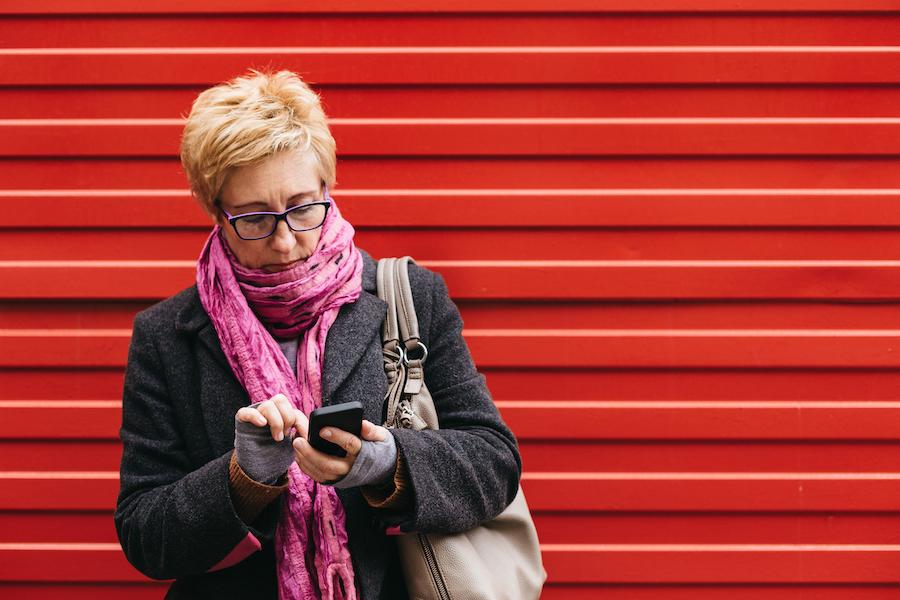 Kvinne med mobil, rød bakgrunn