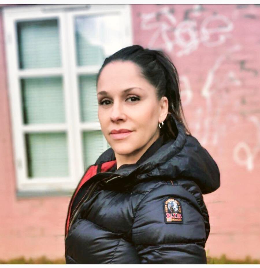 Margrethe Salvesen Zivcic i mørk jakke, rød vegg i bakgrunn