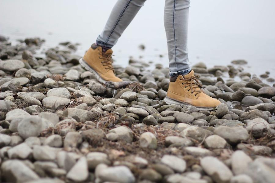 Vandring på steiner, nært av føtter med støvler.