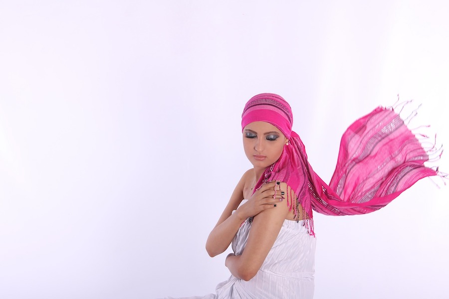 Kvinne med rosa sjal på hodet som blafrer bak henne, hvit bakgrunn