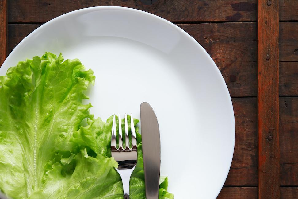 Nært bilde av hvit tallerken med salatblader, kniv og gaffel