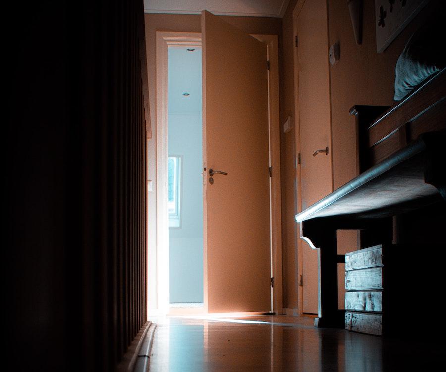 mørkt rom med dør mot lyset utenfor