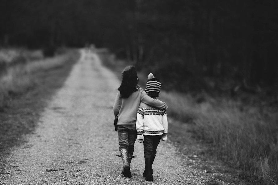 to barn går på en landevei arm i arm. Med ryggen til, bildet i sort hvitt.