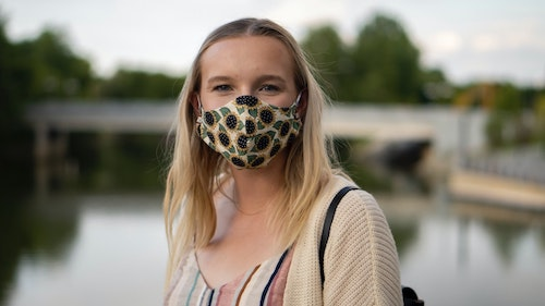 Ung jente med munnbind, trær og vann i bakgrunnen