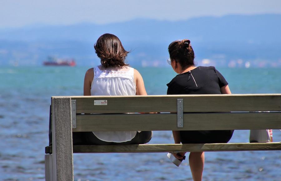 to kvinner sitter på en benk med ryggen til